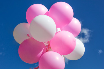 Balloons, pink and white on a background of blue sky with clouds.
