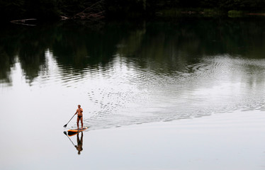 A man paddles on his board on a lake near the town of Uherske Hradiste