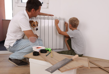 Family and happiness. Father teaching son to repair things at home