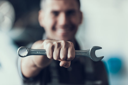 Auto Mechanic with Tool on Blurred Background