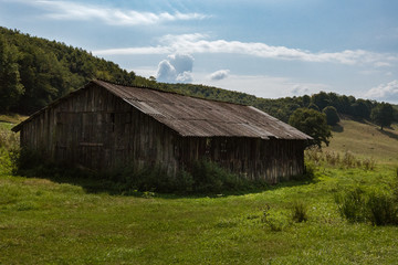 A barn on a green meadow with haystacks on a sunny day with blue sky and white clouds.