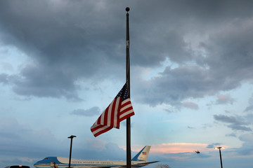 U.S. flag is seen at half-staff as Marine One helicopter with President Donald Trump on board departs