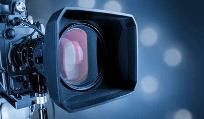Close-up of a television camera lens on blurred background