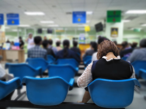 young woman sit on blue chair at front the emergency room and many people waiting medical and health services to the hospital,patients waiting treatment at the hospital,blurred image of people