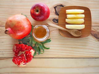 Apples, pomegranates and honey on the wooden board have space for text or symbol with the concept food selected at the Jewish holiday rosh hashanah.