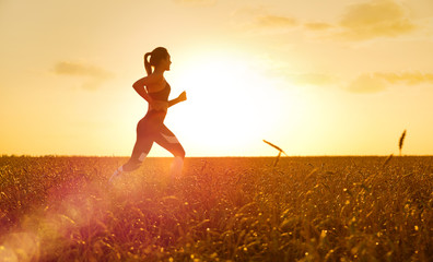 Sporty woman at sunset in wheat field