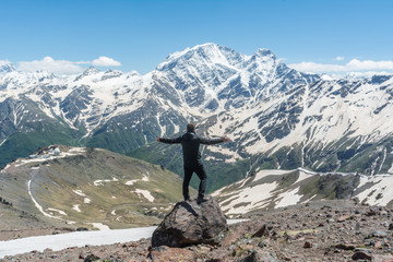 A man stands on a rock and looks at the mountains with arms outstretched.