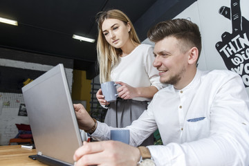 A picture of businessman sitting at table. He is looking at laptop nad holding hand near it. Girl is standing besides man and holds a cup of coffee. She looks at the laptop screen