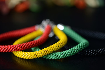 Bead crochet bracelet in Jamaican style on a dark background close up