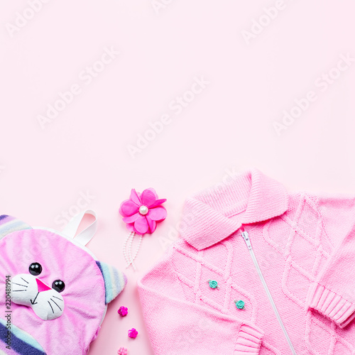 fc6c55ab653f Little girl clothes collection flat lay with cardigan, backpack on pink  background.