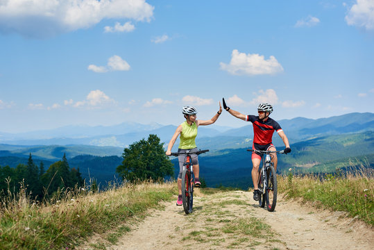 Happy couple bicyclists in professional sportswear and helmets riding cross country bicycles on the mountain road on sunny summer day in Carpathians. Active man and woman giving each other a high five