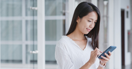 Woman looking for app on cellphone inside shopping mall