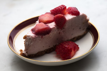 slice of strawberry cheesecake on white background, selective focus