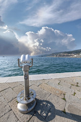 Binocolo fronte mare per vedere lontano in una giornata di sole e vento