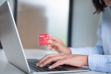Online payment,Woman's using computer laptop and hand holding credit card for online shopping.
