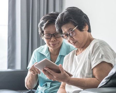Aging society concept with Asian elderly senior adult women twin sisters using mobile digital tablet application technology for social media network among friends community via internet communication