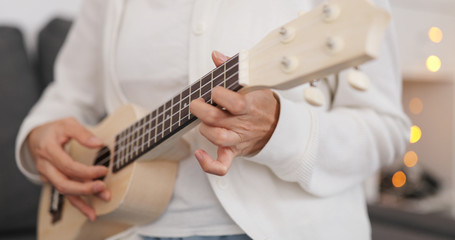 Woman practicing ukulele at home