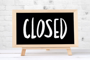 Closed sign on chalkboard standing on white table over white brick wall background