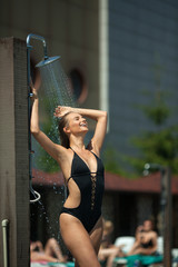 beautiful young girl in a black swimsuit near the pool in the summer takes a shower