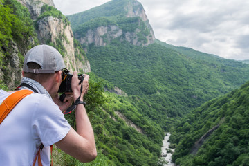 A man takes pictures of nature with a digital camera.