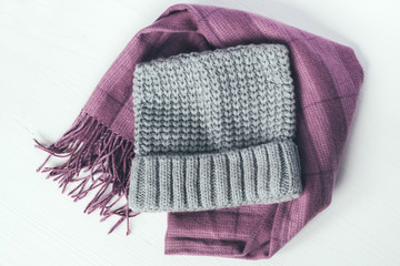 Gray woolen knitted hat and pink scarf on a white background