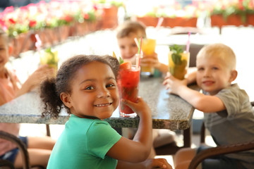 Cute children with glasses of natural lemonades at table in cafe