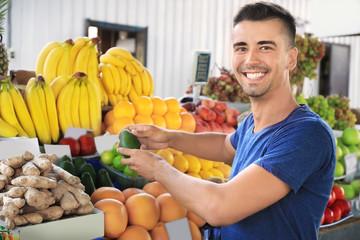 Young man choosing fruits at market