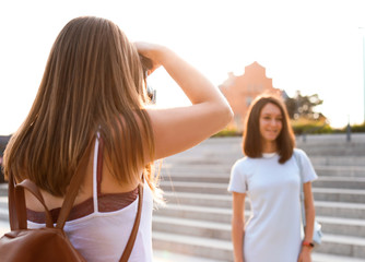 Young woman taking photo of her friend outdoors