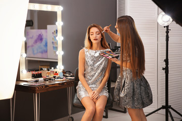 Professional makeup artist working with attractive young woman indoors