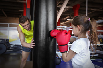 Little girl training with coach and punchbag in boxing gym