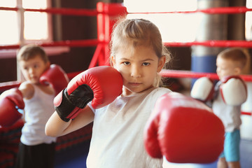 Little girl in boxing gloves on ring