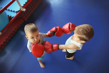 Little boys fighting in boxing ring