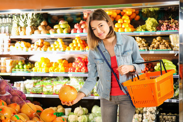 Beautiful woman choosing fresh pomelo fruit in supermarket