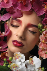 Young woman with dyed eyebrows surrounded by flowers