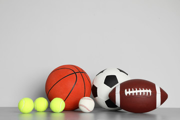 Different sport balls on table against color background. Space for text