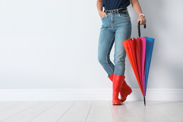 Wall Mural - Woman in gumboots holding bright umbrella near white wall with space for design