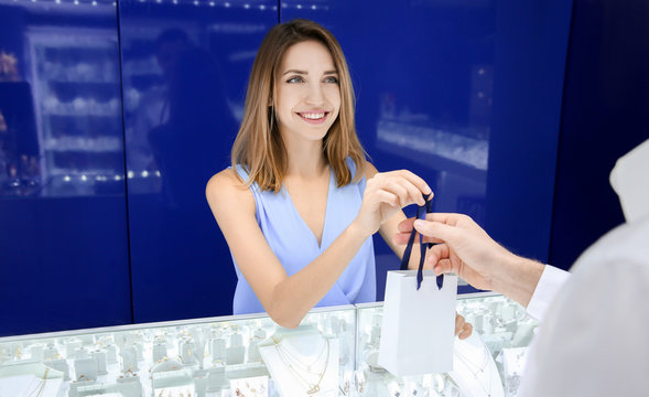 Young shop assistant giving purchase to customer in jewelry store