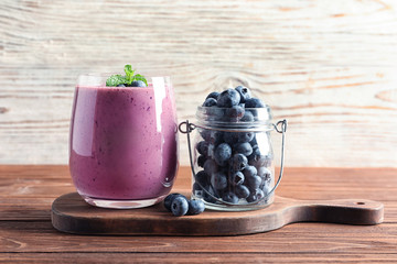Glass of smoothie and jar with blueberries on wooden table