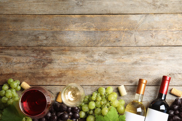 Flat lay composition with fresh ripe juicy grapes and space for text on wooden background