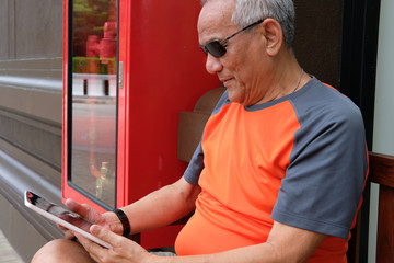 elder man holding tablet. elderly senior male texting message, using app with touchpad outdoor