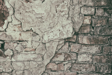 Retro background of old brick wall with fallen off cement plaster
