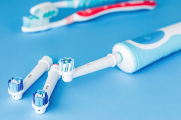 Electric and manual toothbrush  on blue background