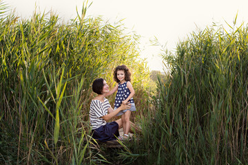 Beautiful and lovely mother with a little daughter secrets in the reeds on the lake