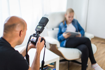 Teenage fashion model being shot by a photographer in a studio