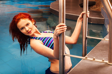 Beautiful woman with red hair relaxing in the pool.
