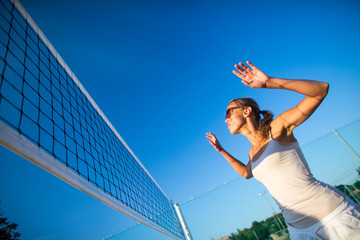 Beach Volleyball Game - Pretty, young woman playing volleyball outdoors