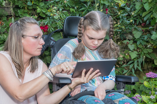 Disability a disabled child learning with help from a special needs carer
