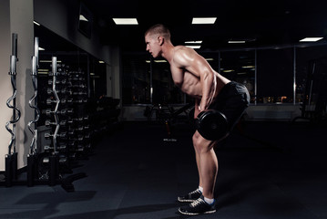Athletic young man doing exercises with barbell in gym. Handsome muscular bodybuilder guy is working out.