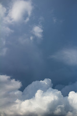 white cumulus clouds on dark blue sky vertical photo