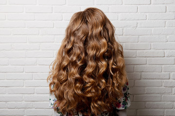 Hairstyle long curls on the head of a brown-haired woman at the back close-up against a white brick wall. Wall mural